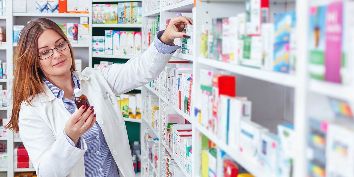 Apothekerin steht vor Medizinregal