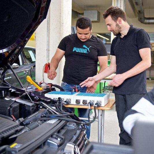 Auszubildender Automechaniker steht an Auto