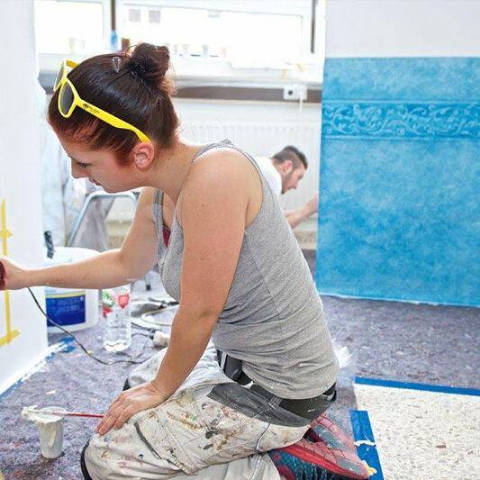 Auszubildende Malerin föhnt Farbe