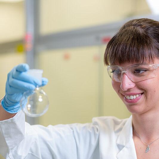 Chemielaborantin mit Glaskolben