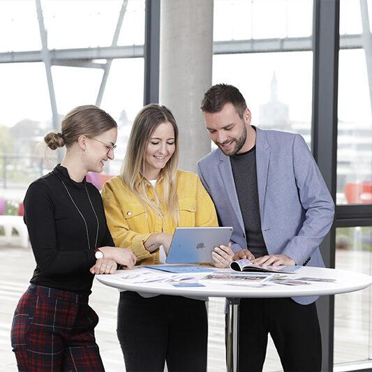 Drei Personen schauen lachend auf ein iPad
