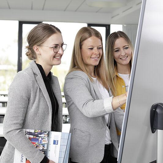 Drei Frauen stehen vor Whiteboard