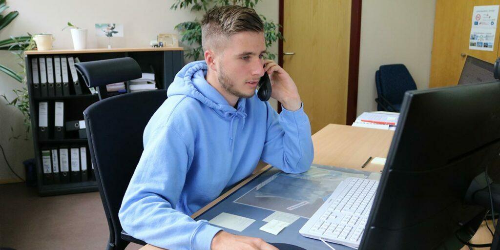 Auszubildender sitzt vor Computer und telefoniert