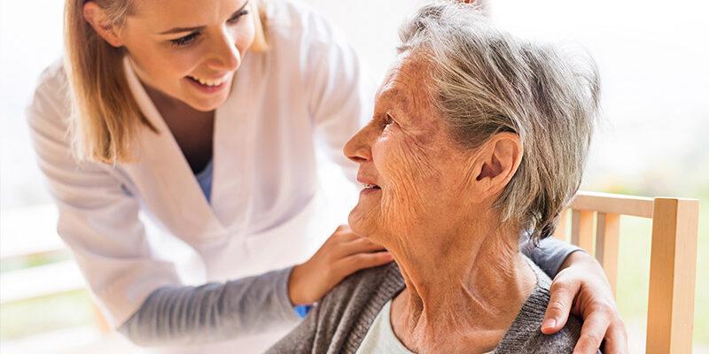 Pflegerin spricht mit alter Frau